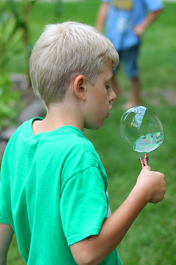 Catching a bubble on Apple Cinnamon Stick Bubble Wands - Inner Child Learning